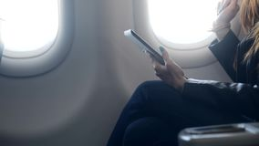 Woman sitting in comfort airplane with tablet stock footage