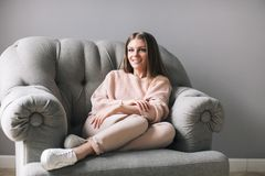Woman sitting on comfortable chair at home. Young woman sitting on comfortable chair at home Stock Photography