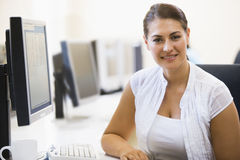 Woman sitting in computer room smiling. At camera Royalty Free Stock Photos