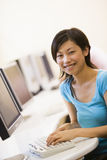 Woman sitting in computer room typing and smiling. At camera Stock Images