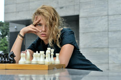 Woman sitting on the contrary chess pieces. She has long blonde hair and she is beautiful stock image