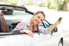 Woman sitting in a convertible car with the keys in hand - conce. Young pretty woman sitting in a convertible car with the keys in hand - concept of buying a Royalty Free Stock Images