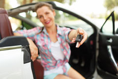 Woman sitting in a convertible car with the keys in hand - conce. Young pretty woman sitting in a convertible car with the keys in hand - concept of buying a Stock Images