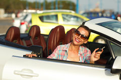 Woman sitting in a convertible car with the keys in hand - conce. Young pretty woman sitting in a convertible car with the keys in hand - concept of buying a Royalty Free Stock Image