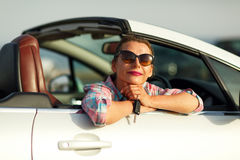 Woman sitting in a convertible car with the keys in hand - conce. Young pretty woman sitting in a convertible car with the keys in hand - concept of buying a Stock Image