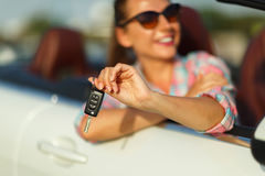 Woman sitting in a convertible car with the keys in hand - conce. Young pretty woman sitting in a convertible car with the keys in hand - concept of buying a Royalty Free Stock Photography