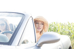 Woman sitting in convertible with female friend on sunny day Stock Photo