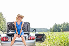 Woman sitting on convertible trunk against clear sky Royalty Free Stock Image