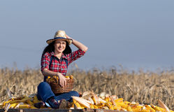 Woman sitting on corn pile Stock Photos
