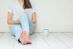 Woman sitting at the corner of house for reading a book in free Stock Images