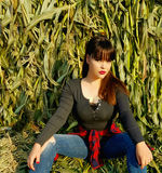 Fashion portrait of beautiful woman in cornfield. Beautiful woman with brown straight hair posing on cornfield among green leaves of maize and intently looks at Stock Image