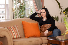 Woman sitting on a couch Royalty Free Stock Photo