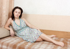 Woman sitting on a couch royalty free stock photography