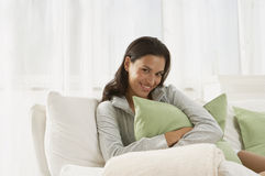 A woman sitting on a couch. A woman sitting on a couch stock image