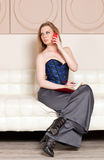 Woman sitting on the couch Stock Image