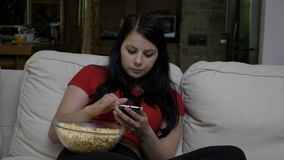 Woman sitting on the couch with a bowl of popcorn and texting on smart phone during tv commercial break. Woman sitting on the couch with a bowl of popcorn in her stock video footage