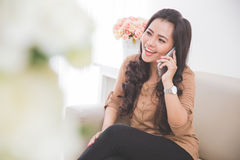 Woman sitting on a couch, calling friend with smartphone royalty free stock photo
