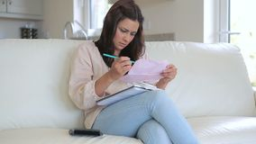 Woman sitting on the couch checking the bills. Video of woman sitting on the couch in living room checking the bills stock footage