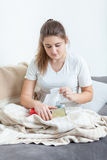 Woman sitting on couch covered in blanket and pulling tissues Royalty Free Stock Image
