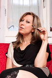 woman sitting on couch with electric cigarette Royalty Free Stock Photo