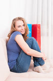 Woman sitting on couch feeling comfy and smiling. With shopping bags around with copy space area Stock Images