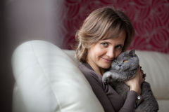 Woman sitting on the couch and fondles gray cat Royalty Free Stock Photo