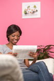Woman sitting on couch with fresh newspaper. Royalty Free Stock Photos
