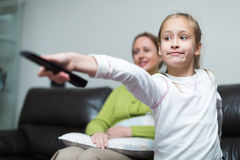 Woman sitting on couch and girl holding remote control Stock Photo