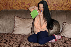 Woman sitting on a couch with a green notebook Stock Photos