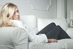 Young beautiful woman sitting on couch at her room