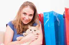 Woman sitting on couch holding cat with shopping bags Stock Photos
