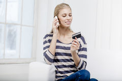 Woman sitting on the couch and holding credit card Royalty Free Stock Photography