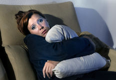 Woman sitting on couch holding pillow against chest in stress and depression Stock Photos