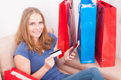 Woman sitting on couch holding smartphone showing credit card Stock Images