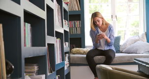 Woman Sitting On Couch In Home Office Using Mobile Phone. Young woman sitting on couch using mobile phone at home.Shot in 4k on Sony FS700 at frame rate of 25fps stock footage
