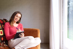 Woman sitting on couch at home and writing in book. Portrait of a woman sitting on couch at home and writing in book Royalty Free Stock Image