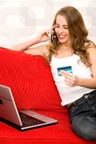 Woman sitting on couch with laptop Royalty Free Stock Photos