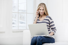 Woman sitting on the couch with laptop Stock Images