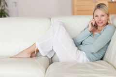 Woman sitting on the couch listening to caller Stock Images