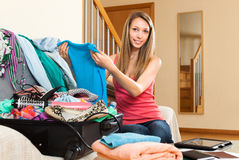 Woman sitting on couch near opened suitcase. Relaxed young woman sitting on couch near opened overfull suitcase Stock Images