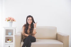Woman sitting on a couch, pointing to blank white wall up Royalty Free Stock Photography
