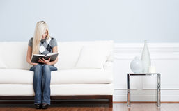 Woman Sitting on Couch and Reading Book Royalty Free Stock Photos