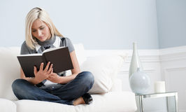 Woman Sitting on Couch and Reading a Book Stock Photo