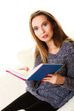 Woman sitting on couch reading book at home Stock Photos
