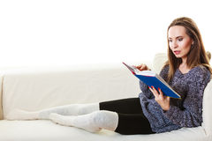 Woman sitting on couch reading book at home Royalty Free Stock Photography