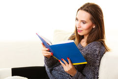 Woman sitting on couch reading book at home Stock Image