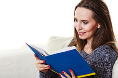 Woman sitting on couch reading book at home Royalty Free Stock Images