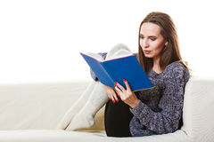 Woman sitting on couch reading book at home Royalty Free Stock Photos