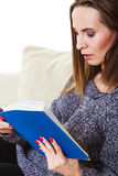 Woman sitting on couch reading book at home Royalty Free Stock Photo