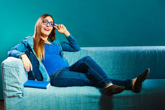 Woman sitting on couch reading book at home Stock Images